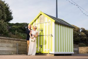 bride and groom with beach hut at felixstowe