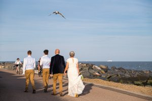 bride and groom walking on the prom at felixstowe